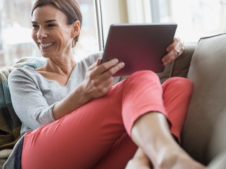 woman in red trousers on sofa holding a tablet