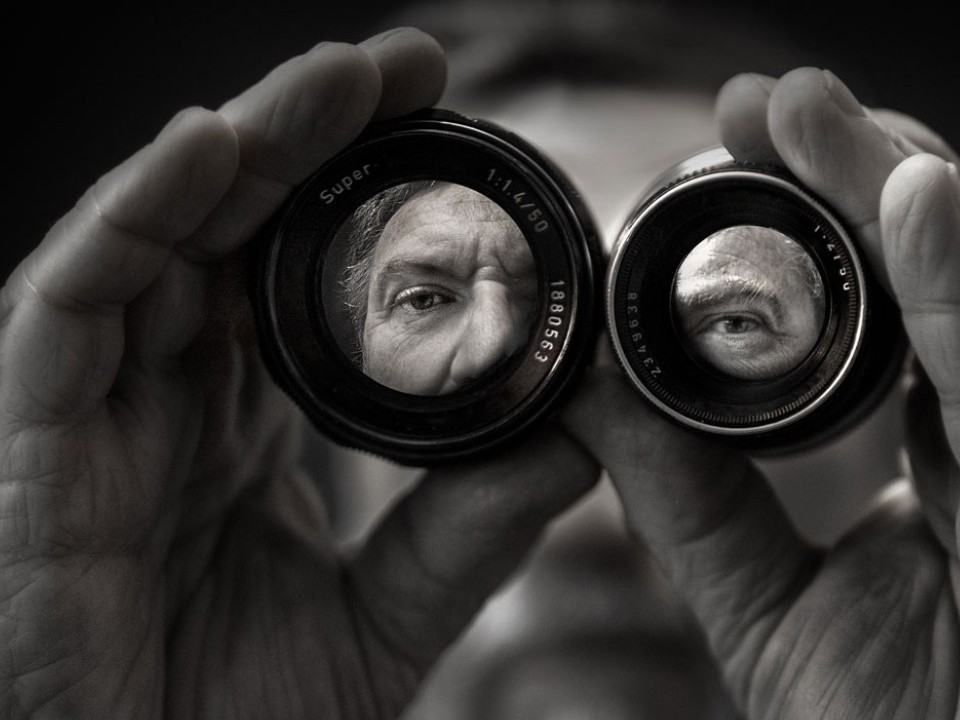 Man peering through two camera lenses side by side